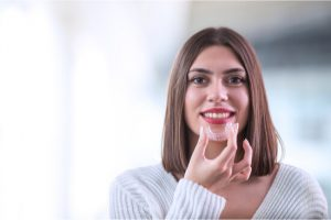 woman holding invisalign