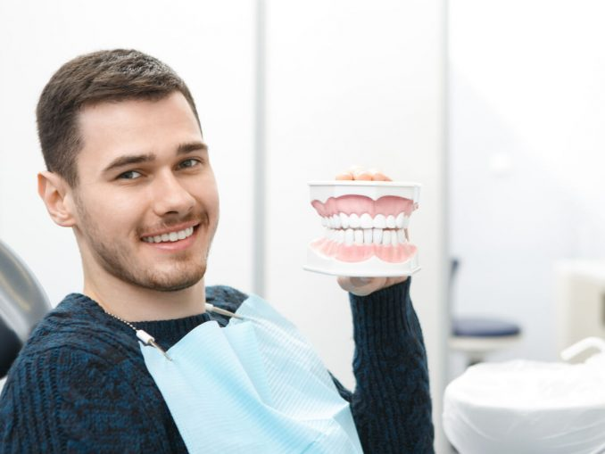 The patient holds an artificial dental model.
